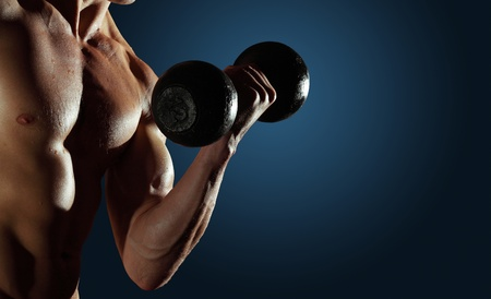 dumbells: Part of a mans body with metal dumbbell on a blue background Stock Photo