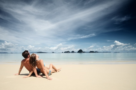 Young couple sitting together on a sand and looking to the horizon photo