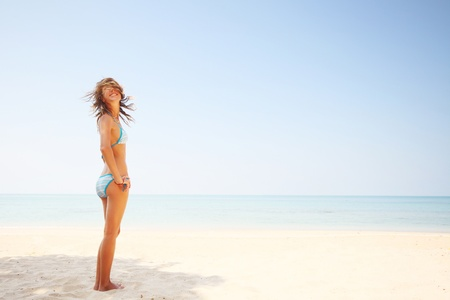 hot body girl: Happy smiling woman on a sunny beach with clear sky Stock Photo