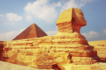 Sphinx statue and pyramid of Cheops on the background. Giza plateau in Egypt photo