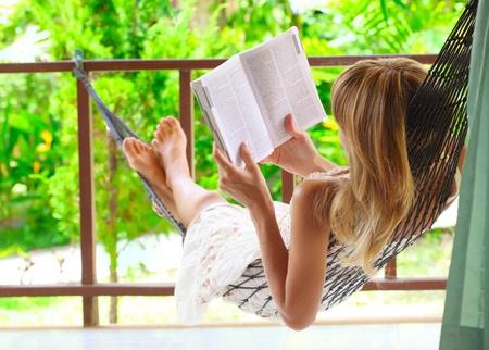 hammocks: Giovane donna giace in una amaca in giardino e la lettura di un libro Archivio Fotografico