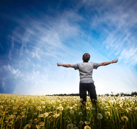 free time: Young man standing on a meadow with raised hands Stock Photo