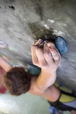 Young man climbing indoor wall photo
