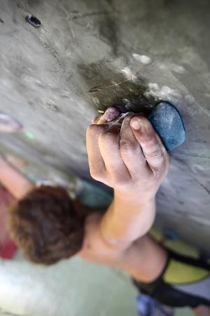 Young man climbing indoor wall photo
