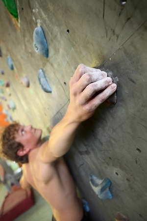 Young man climbing indoor wall Stock Photo - 11541056
