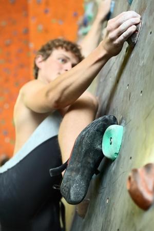 bouldering: Young man climbing indoor wall