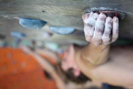 escalando: Hombre joven muro de escalada indoor
