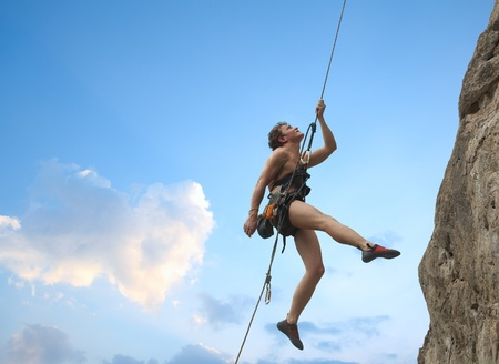 free climbing: Young man hanging on a rope by a rocky wall over blue sky background