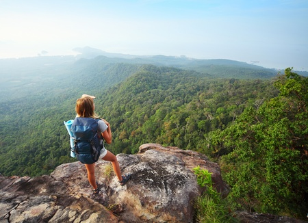 Young woman standing with backpack on cliffs edge and looking to the horizon photo