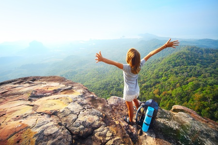 Young woman standing with backpack on cliff's edge and looking to a sky photo
