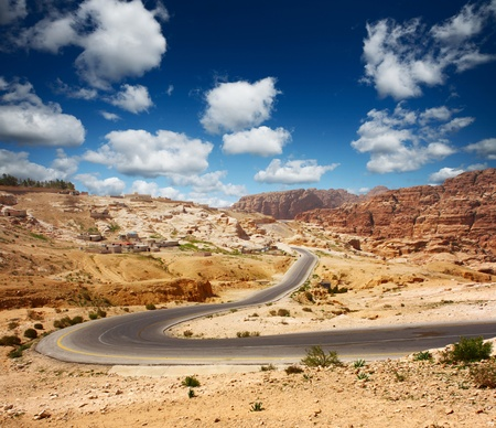 side road: Asphalt road in a desert with blue cloudy sky on the background
