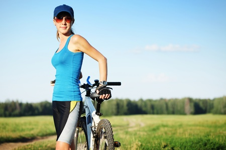 Young slender woman in red glasses standing by bicycle and looking to a camera Stock Photo - 11540760