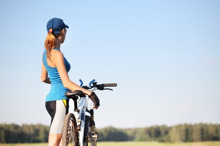 Young slender woman standing by bicycle and looking to a sky.