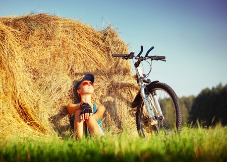 Young woman with bicycle sitting near straw heap and looking to a sky photo