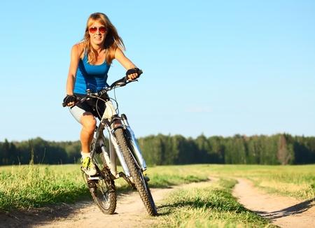 andando en bicicleta: Mujer joven montado en una bicicleta por un camino rural Foto de archivo
