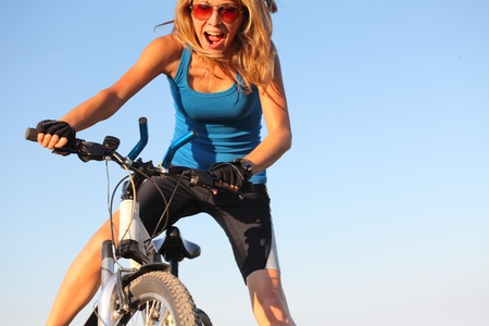 bawl: Young woman holding handlebar of a bicycle and shouting