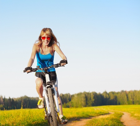 Woman in red glasses riding on a bicycle on a countryside road photo