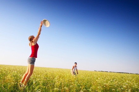 frisbee: Young couple playing frisbee on a green meadow with grass on clear blue sky background Stock Photo