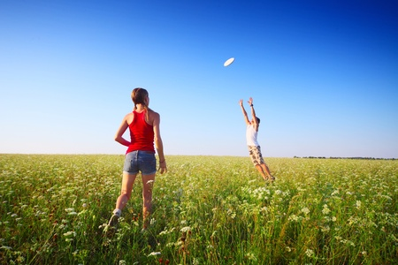 Young couple playing frisbee on a green meadow with grass on clear blue sky background. Focus on a woman photo