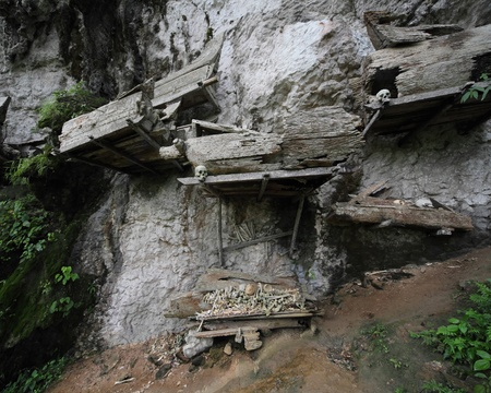 coffins: Groups of old family coffins with bones hanging on a rock. Tana Toraja region. Sulawesi island. Indonesia Stock Photo