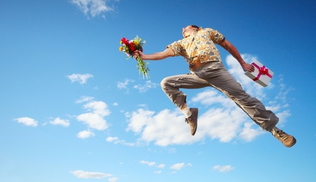 Young happy man jumping with flowers and gift box on blue sky background Stock Photo - 11541052