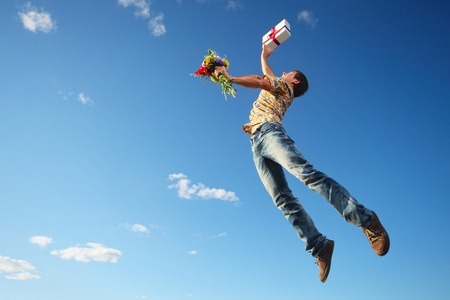 man flying: Young man jumping with flowers and gift box on blue sky background