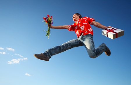 Young smiling man jumping with flowers and gift box on blue sky background photo