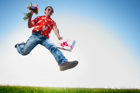 Young happy man in sunglasses jumping with flowers and gift box on blue sky background photo