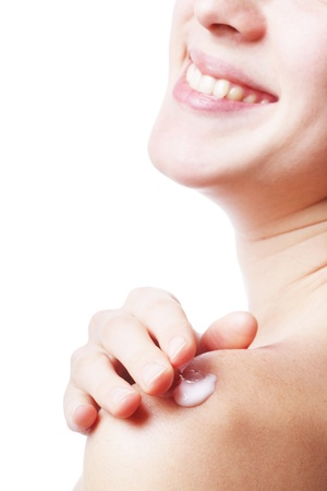 Smiling woman putting white cream on her shoulder photo