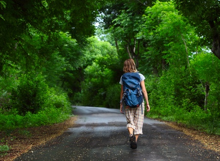 Woman with backpack walking on a wet road among green tropical trees photo