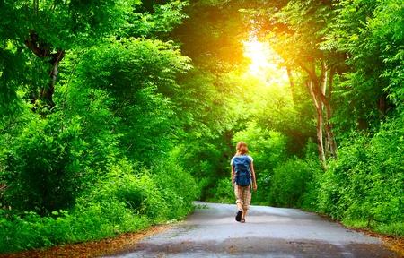 熱帯は緑の木々 の中で濡れた道路の上を歩いてのバックパックを持つ女性