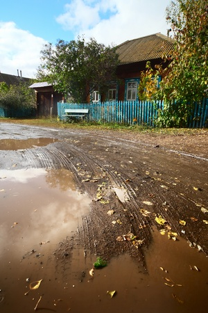 mud house: Wet muddy autumn road in a village with wooden houses