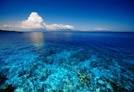 Blue shallow sea with coral reef and fluffy clouds on the horizon photo