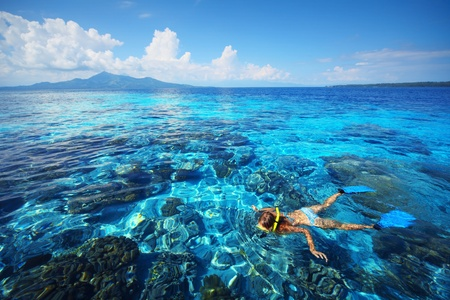 Young woman snorkeling in transparent shallow blue sea above coral reef. photo