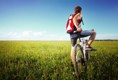 Young man standing with bicycle on a green grass and looking to the horizon photo