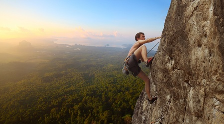 Young man climbs on a rocky wall in a valley with mountains at sunrise photo