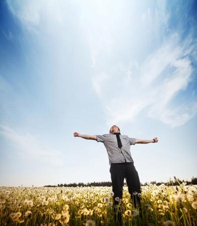 libertad: Joven de pie en un prado con las manos levantadas Foto de archivo