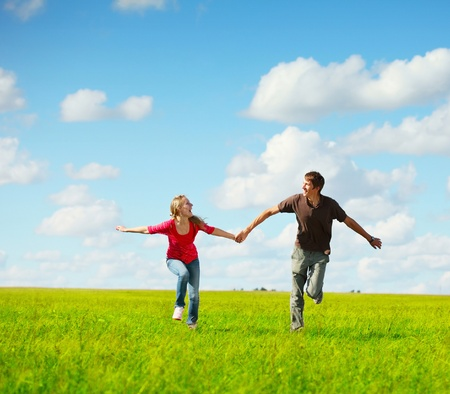 Young happy family running on a green meadow photo