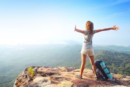 Young woman standing with backpack on cliffs edge and looking into a wide valley photo
