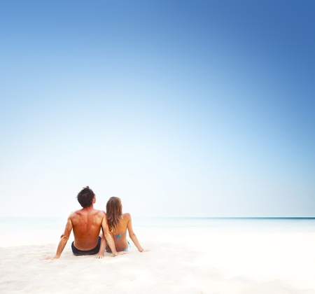 Young couple sitting on white sand by sea and enjoying each other photo