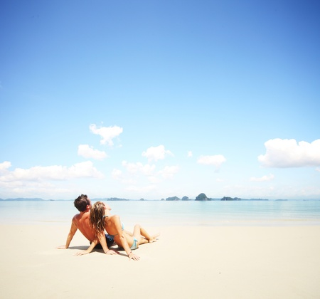 Young happy couple sitting on a sand by sea and looking to a sky Stock Photo - 11540837