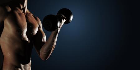 levantar pesas: Parte del cuerpo de un hombre mojado con mancuernas de metal sobre un fondo oscuro