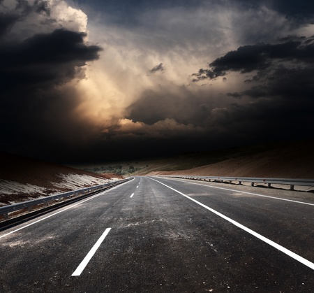Dirty asphalt road and dark thunder clouds Stock Photo - 11540921