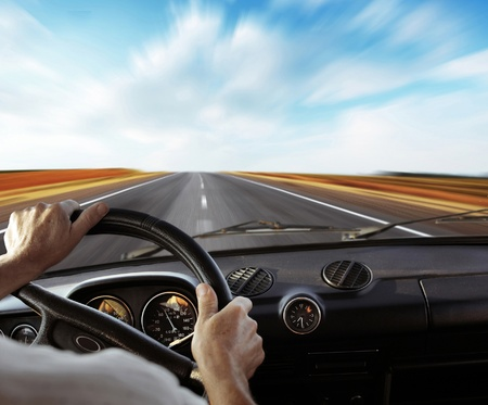Drivers hands on a steering wheel with motion blurred road and sky