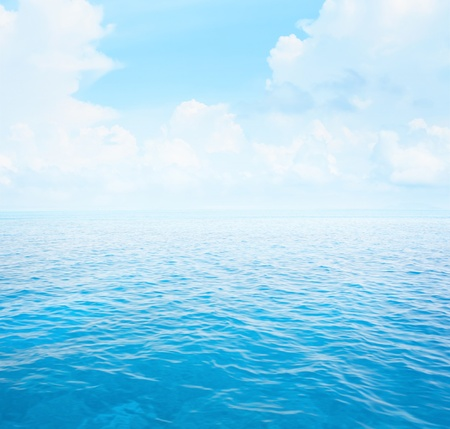 Blue clear sea with waves and sky with fluffy clouds photo