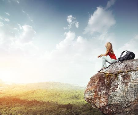 mujer mirando el horizonte: Mujer joven con mochila sentado en borde del acantilado y mirando a un cielo con nubes Foto de archivo