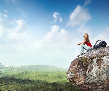 mochila: Mujer joven con mochila sentado en borde del acantilado y mirando a un cielo con nubes Foto de archivo