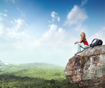 trekker: Young woman with backpack sitting on cliffs edge and looking to a sky with clouds