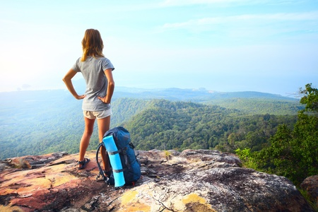 Young woman standing with backpack on cliffs edge and looking into a wide valley Stock Photo