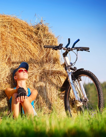 space weather tire: Young woman with bicycle sitting near straw heap and looking to a sky Stock Photo